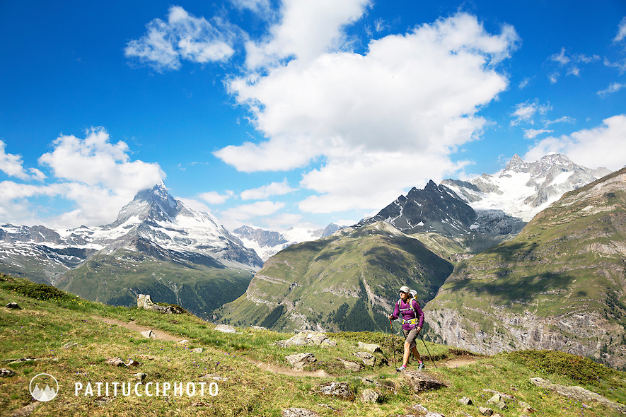 A woman hiking in the dramatic landscape high above Zermatt, Switzerland with the Obergabelhorn and Matterhorn in the background