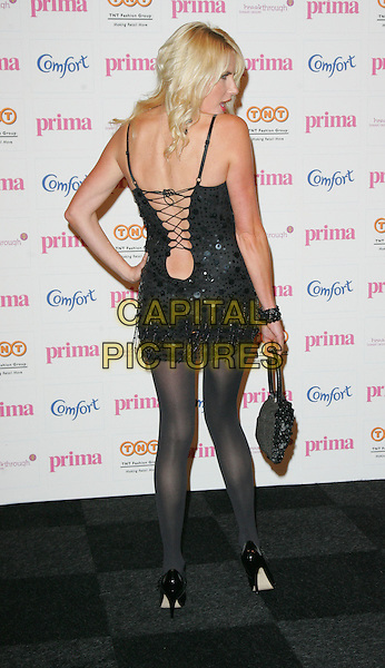 NANCY SORRELL .Comfort Prima High Street Fashion Awards at the Battersea Evolution, London, England, September 11th 2008..full length black dress hand on hip tights bag sequined mary jane shoes back over shoulder rear behind lace-up corset .CAP/ROS.©Steve Ross/Capital Pictures