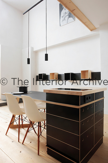 "In this kitchen-diner a dining table, hob and kitchen cupboard are all integrated in the central island which is made of plywood and finished in black linoleum; the dining chairs are the ""Plastic Side Chair"" design by Charles Eames"