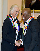 Jimmy Page of Led Zeppelin and Buddy Guy, two of the seven recipients of the 2012 Kennedy Center Honors, shake hands as they prepare to pose for a photo following a dinner hosted by United States Secretary of State Hillary Rodham Clinton at the U.S. Department of State in Washington, D.C. on Saturday, December 1, 2012.  The 2012 honorees are Buddy Guy, actor Dustin Hoffman, late-night host David Letterman, dancer Natalia Makarova, and the British rock band Led Zeppelin (Robert Plant, Jimmy Page, and John Paul Jones)..Credit: Ron Sachs / CNP