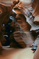 Male photographer in the upper Antelope slot canyon on the Colorado Plateau near Lake Powell and Page Arizona
