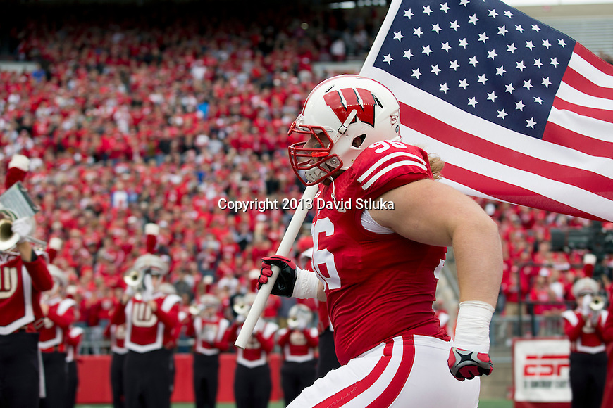 Wisconsin Badgers defensive lineman Beau Allen (96) leads the team out of the tunnel carrying the American flag during an NCAA Big Ten Conference football game against the Purdue Boilermakers on Saturday, September 21, 2013, in Madison, Wis. The Badgers won 41-10. (Photo by David Stluka)