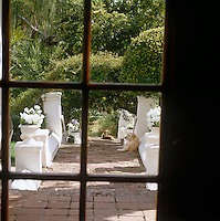 Seen through the glass panes of the back door a brick path is flanked by white-painted stone walls with urns planted with white gernaniums creating a white-on-white theme