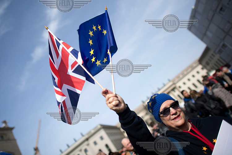 A woman waves a Union Jack and an EU flag at a pro-EU rally, the 'March for Europe', organised by the European Movement to celebrate the 60th anniversary of the Treaty of Rome.