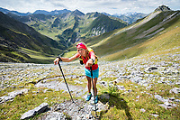 A woman trail runner stops to rest on her poles while doing a trail from Weisstanenntal to the Pizol, Switzerland