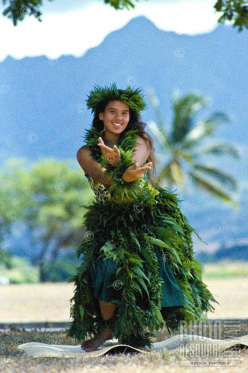Young woman performing hula kahiko (traditional hula)