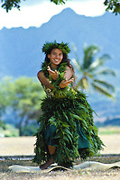 Young woman performing hula kahiko (traditional hula)