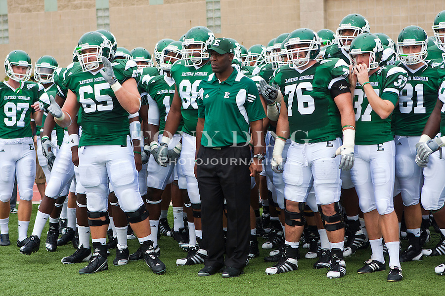 Eastern Michigan head coach Ron English, center, lines up with his players before taking the field before the first quarter of an NCAA college football game, Saturday, Sept. 18, 2010, in Ypsilanti, Mich. (AP Photo/Tony Ding)