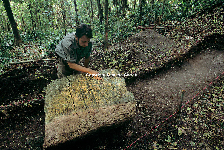 Archaeologist examines stele, Cival, Holmul, Guatemala, Maya, Francisco Estradabelli