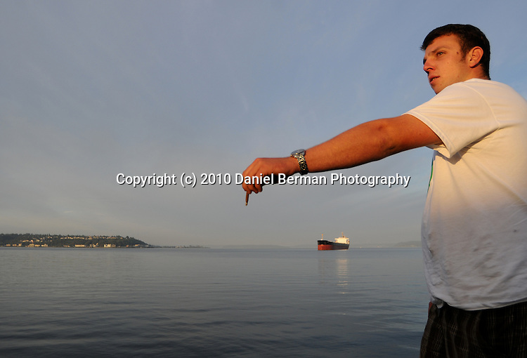 Seattle Hempfest - August 21-22, 2010 in Myrtle Edwards Park. An attendee passes a lit blunt to his friend, out of frame, on the shores of Elliott Bay. Photo by Seattle photographer Daniel Berman