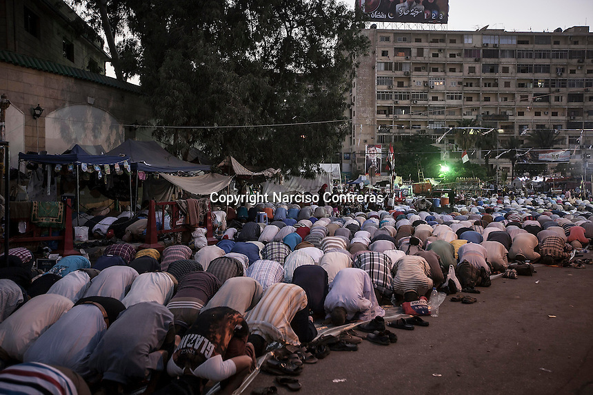In this Wednesday, Jul. 10, 2013 photo, supporters of the ousted president Mohammed Morsi offer prayers (Taraweeh) before dusk in the streets nearby Al-Rabba Alawya mosque during the first day of the holy month of Ramadan in Cairo, Egypt. (Photo/Narciso Contreras).