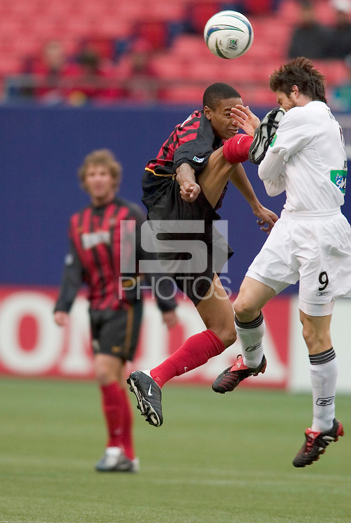 New England Revolution's Joe-Max Moore gets to see what shoe size the MetroStars' Ricardo Clark wears. The New England Revolution played the NY/NJ MetroStars to a 1 to 1 tie at Giant's Stadium, East Rutherford, NJ, on April 24, 2004.