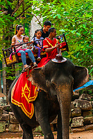 Tourists riding an elephant with The Bayon behind, Angkor Thom, Cambodia.