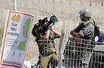 Israeli soldiers watch the  Palestinians celebration next a board which demand to remove the apartheid wall and end occupation  near  Israel's controversial separation wall near the West Bank village of Bilin. Palestinians celebrated a ruling by Israel's Supreme Court that a part of the controversial separation barrier near Bilin must be rerouted.