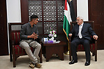 Palestinian President Mahmoud Abbas meets with Firas Bassam Abu Awwad, 17, who was lost his family in a traffic accident with an Israeli military vehicle in 2010, at his headquarter in the West Bank city of Ramallah on August 8, 2017. Photo by Osama Falah
