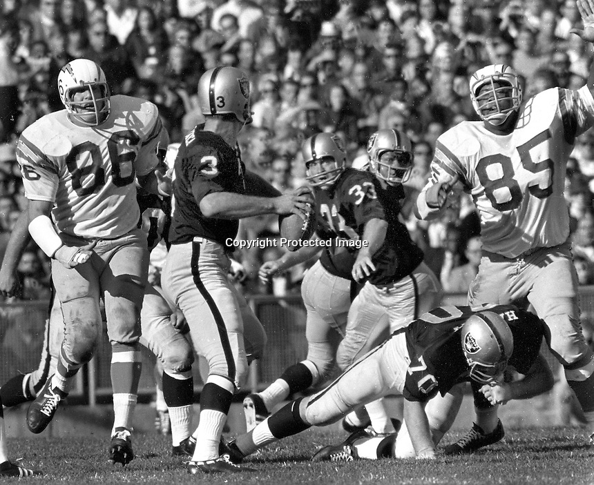 Raiders Daryle Lamonica ready to pass against the San Diego Chargers # 86 Earl Faison and #85 Bob Petrich.   (1967 photo/Ron Riesterer)