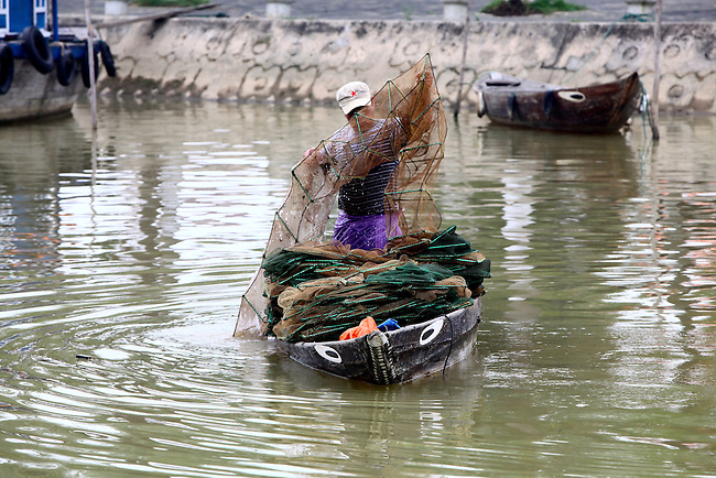 A fisherman hauls up his traps from the river in Hoi An, Vietnam. The city was an important trading port from the 16th to the 19th centuries. The colonial atmosphere and architecture of Hoi An Ancient Town is the most well-preserved in Vietnam. April 22, 2012.