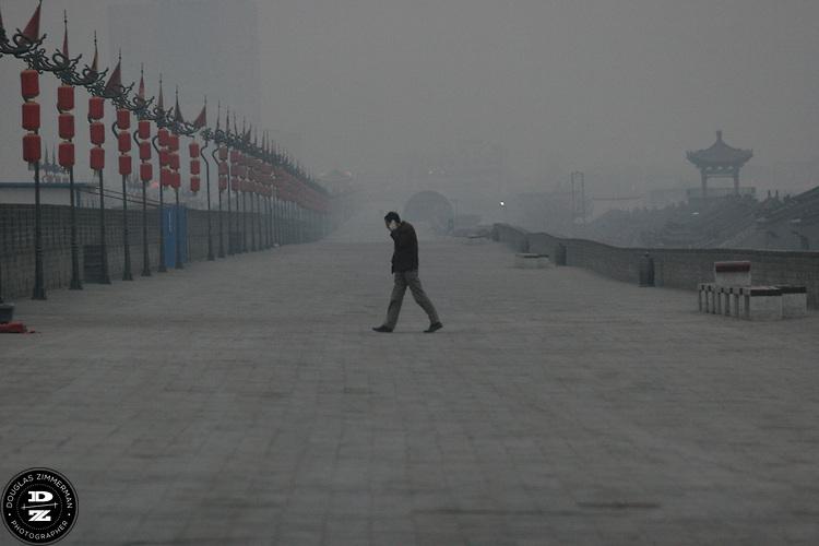 A man walks along the old city wall in Xian, China. . Photograph by Douglas ZImmerman