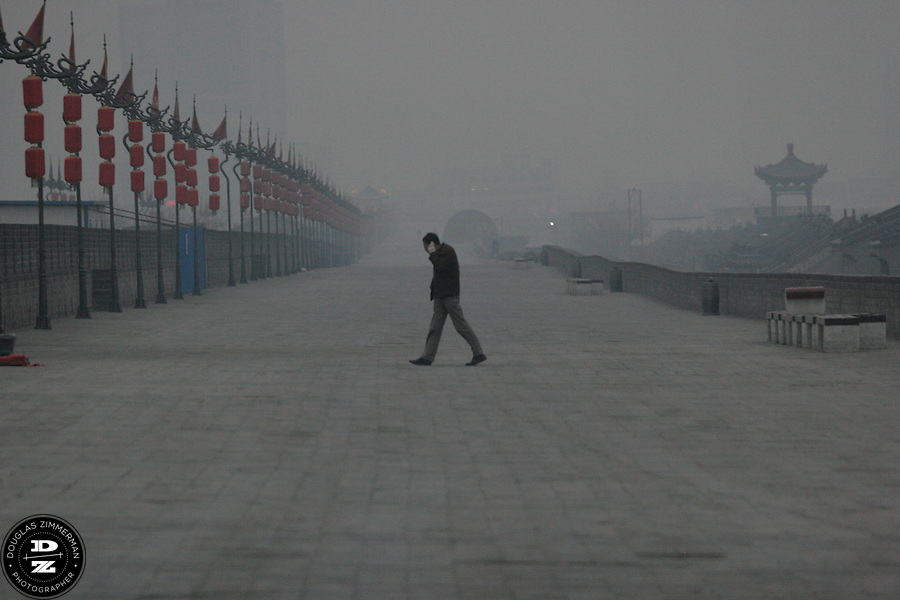 A man walks along the old city wall in Xian, China. . Photograph by Douglas ZImmerman