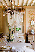 The dining room is decorated with hand-painted wall panels and the table is laid for lunch