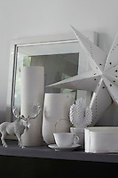 A collection of white objects is displayed on open shelving in the dining area