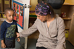 Education Preschool Childcare toddler-2 year olds boy with teacher at start of day encouraging him to come in