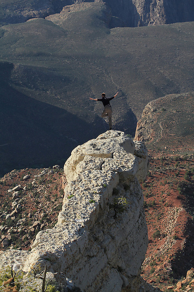 Man balancing on a rock at the edge in Grand Canyon National Park, Arizona. . John offers private photo tours in Grand Canyon National Park and throughout Arizona, Utah and Colorado. Year-round.