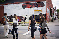 Hipsters walk by an advertisement for Bacardi being painted on a wall in the trendy hipster Williamsburg neighborhood of Brooklyn in New York on Saturday, June 8, 2013. © Richard B. Levine)