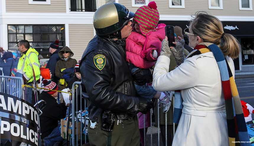 Hampton police officer Peter Moisakis kisses his two-year-old daughter Stephanie as hid wife Megan takes their picture before the start of the Hampton Christmas Parade in Hampton, N.H., Saturday, Dec. 7, 2013.  (Portsmouth Herald Photo Cheryl Senter)