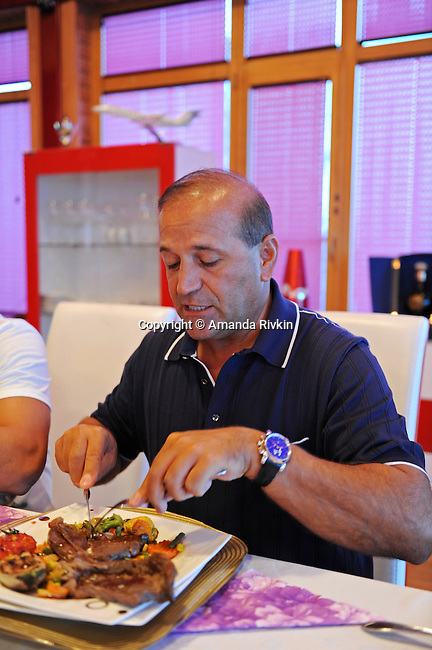 Ibrahim Ibrahimov eats a steak for dinner in his home between Sangachal and Sahil, Azerbaijan on August 16, 2012.