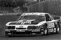 MIAMI, FL - MARCH 2: Bruce Jenner, winner of the gold medal for decathlon in the Montreal 1976 Summer Olympics, drives a Jack Roush Ford Mustang during the Xtra Super Food Centers Camel GTO IMSA GTO race on the temporary street circuit in Bicentennial Park in Miami, Florida, on March 2, 1986.