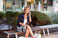 Attractive female shopper talks on a new smart phone at an Austin outdoor shopping mall