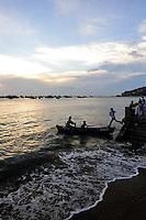 A man jumping from the sea-wall to a small boat, at sunset. Bai Truoc (Front Beach, aka Tam Duong beach), Hang Dua bay, Vung Tau, Vietnam