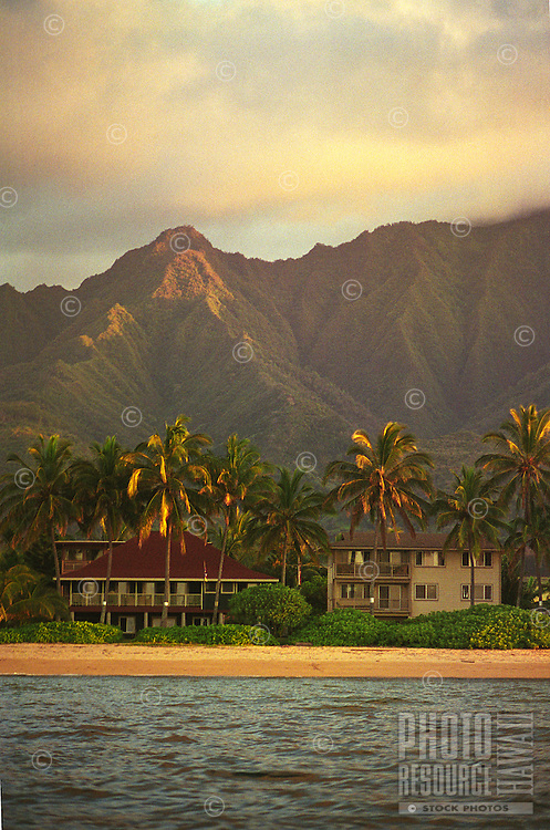 Beachfront vacation rental homes with Mt. Ka'ala in background, shot from sea, in afternoon light, at Waialua, on the North Shore of Oahu