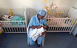 NOT MODEL RELEASED; FOR EDITORIAL USE ONLY... nurse sitting in chair holding an HIV+ infant in South African Shepard's Keep home for abandoned newborns