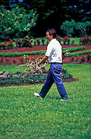 Man walking with golf clubs across greens