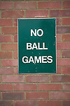 No Ball Games sign on red brick wall