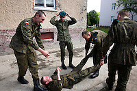 Young soldiers messing about during a cigarette break at the military base in Bartoszyce. This year's class of drafted recruits is the final one after 90 years of compulsory military service, as Poland's army turns professional in 2009.