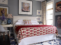 A photograph of Carla Bruni by Michel Comte hangs above the bed dressed in linens and a coverlet by the owner, who also designed the parchment-covered desk and paired it with a classic Charles Eames chair