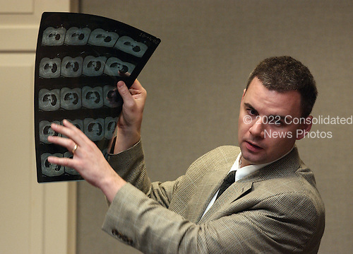 Doctor Kevin Beir holds up a CAT scan detailing the injuries to sniper victim Caroline Seawell during testimony in the trial of sniper suspect John Allen Muhammad in courtroom 10 at the Virginia Beach Circuit Court in Virginia Beach, Virginia on October 28, 2003. <br /> Credit: Adrin Snider - Pool via CNP