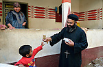 Father Joil Sobhe, a Coptic Orthodox priest, distributes bread to church members in the Egyptian village of Sakra.