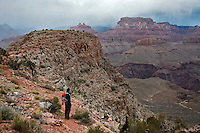 A hiker surveys the inner canyon from Horseshoe Mesa in the Grand Canyon during a November storm.