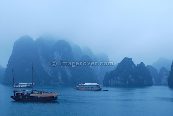 Asia, Vietnam, Halong Bay. Boat trip on the Halong Bay. Early morning after an overnight stop. Designated a UNESCO World Heritage Site in 1994, the sensational Halong Bay is spread across 1.500 sq km, with more than 2.000 pinnacle shaped limestone and dolomite outcrops scattered across it. The impression is a labyrinthine seascape of bizarrly shaped outcrops, isolated caves, and sandy coves.