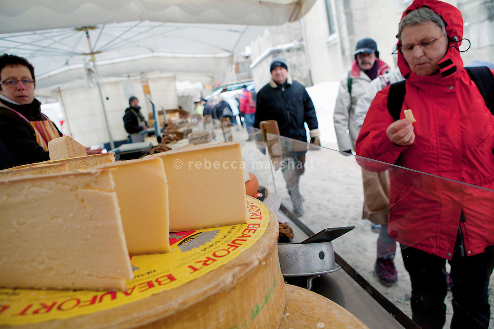 A market-goer tastes Beaufort cheese on sale at the weekly Wednesday morning market, Le Grand Bornand, France, 15 February 2012.