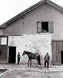 SWITZERLAND, Motiers, Lutin and his wife Giselle du Jura with their horse Clatiola in front of their barn, Jura Region (B&W)