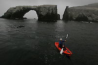 ANACAPA,CA - May 05, 2008: A kayaker navigates around Arch Rock on the east end of Anacapa Island, May 5, 2008. The forty foot tall rock formation is the symbol of the Channel Islands National Park. Channel Islands National Park, off the Southern California coast includes five islands--Santa Cruz, Santa Rosa, San Miguel, Santa Barbara, and Anacapa.