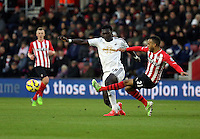 Pictured L-R: Bafetimbi Gomis of Swansea challenged by Ryan Bertrand of Southampton Sunday 01 February 2015<br /> Re: Premier League Southampton v Swansea City FC at ST Mary's Ground, Southampton, UK.