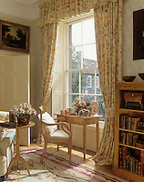A writing table and chair is set before a window in a traditional sitting room. The window is dressed with full length floral pattern curtains with a pelmet. Family photographs in frames are displayed on the table and a bookcase stands to one side.