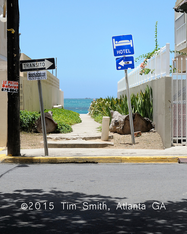 May 21, 2008  Isla Verde, Puerto Rico..A hotel sign points the wrong way down a one-way street in Isla Verde, Puerto Rico...travel, juxtapose, irony, rules, directions, signs, point, arrow, ocean, beach, Puerto Rico, Isla Verde, condos, neighborhood, Se Pintan Bañeras, curb, path