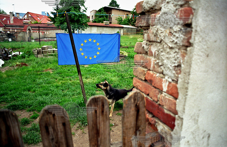 An European Union flag hangs in the garden of a house in the Horni Pocernice districty of Prague at around th etime of the Czech Republic's accession to the EU (1 May 2004).